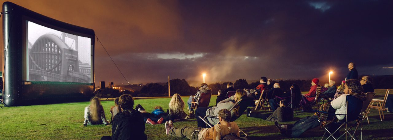 A group of revellers relax in a field to watch a film on a big screen.